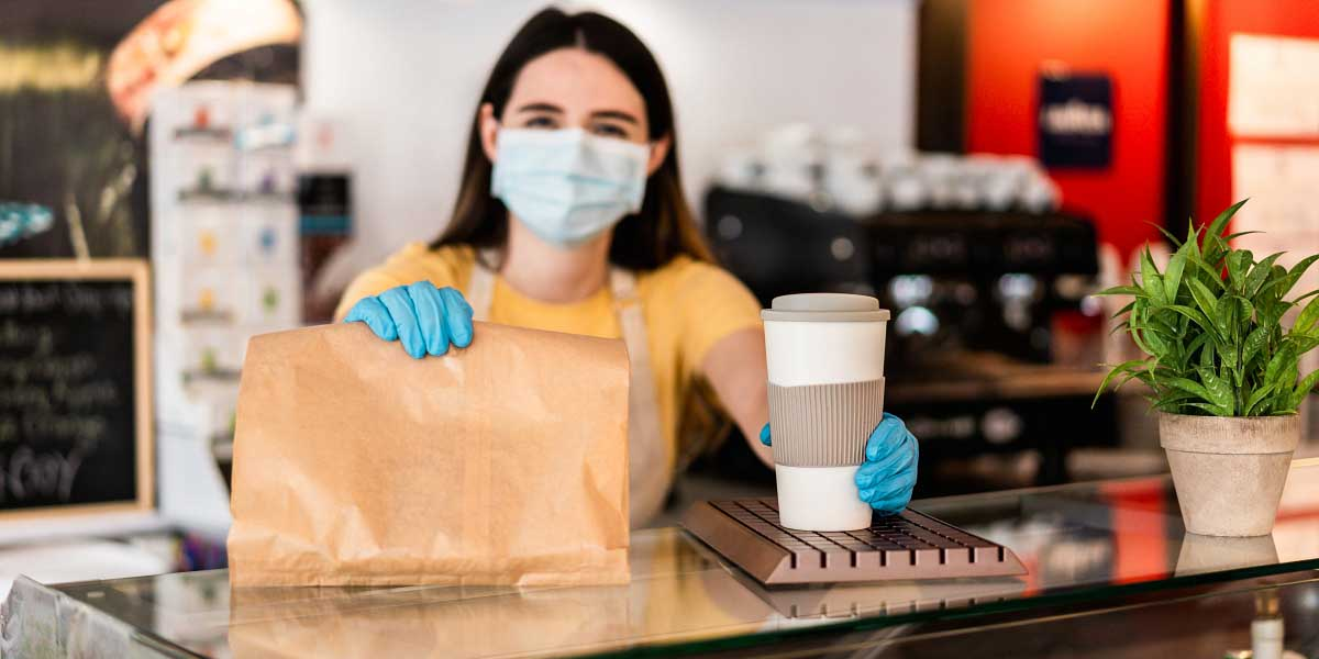 Young woman wearing face mask while serving takeaway breakfast and coffee inside cafeteria restaurant - Worker preparing healthy food inside cafè bar during coronavirus period