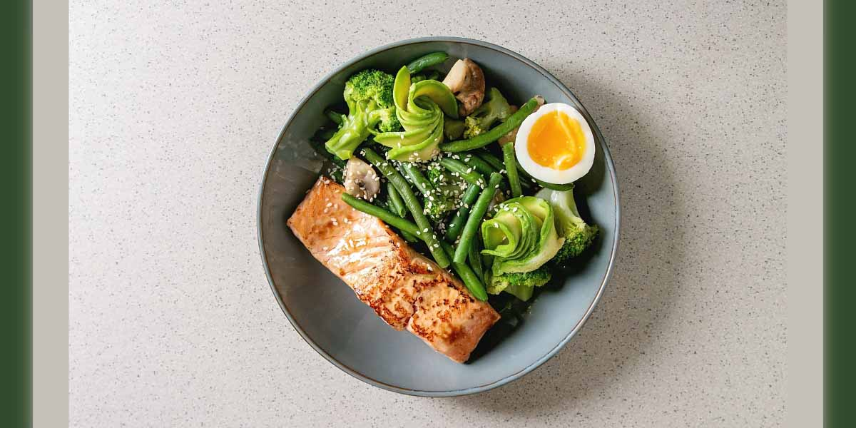 Ketogenic low carb diet dinner grilled salmon, avocado, broccoli, green bean and soft boiled egg in ceramic bowl over grey spotted background