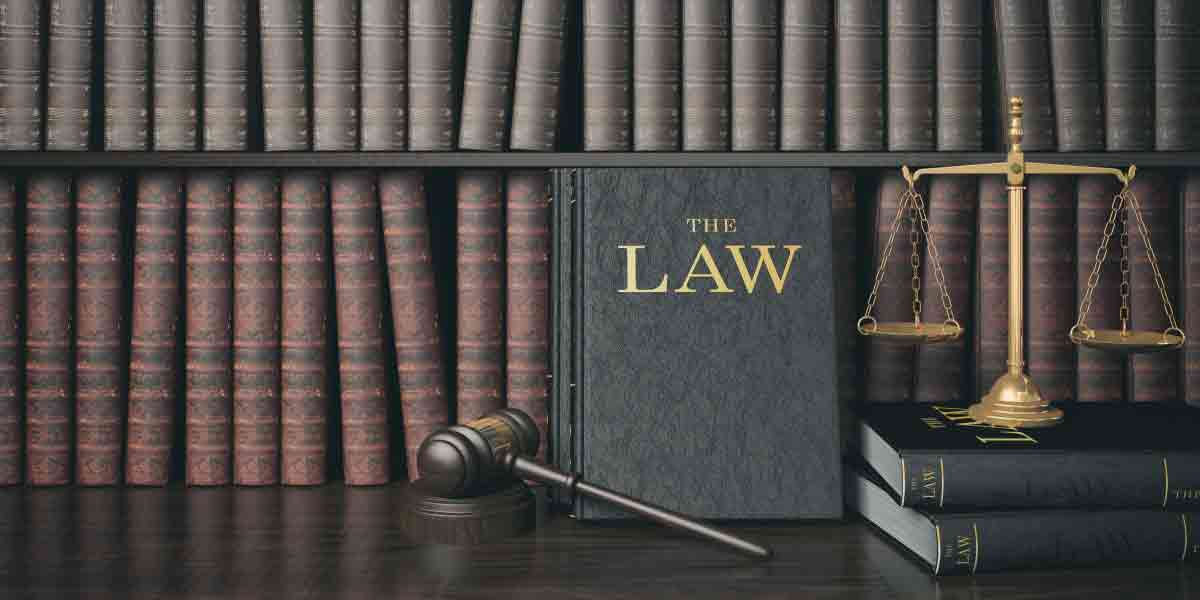 An image of legal books lining a shelf, fronted by a gavel, a book titled the law and the scales of justice on top of two law books.